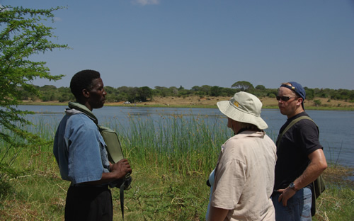 Temba (local Zulu tourist guide) discussing wildlife protection and de-snaring at Muzi Pan with Janet Cuthbertson (Suni-Ridge) and Marcel Koning (guest)